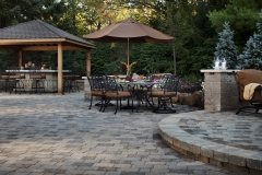 Outdoor living space with patio, fire pit, walls and outdoor dining located in Fishers, Indiana includes Bergerac and Weston Wall. Project designed and completed by McCune Outdoor Living. The project utilized the following Belgard products manufactured by 4D Schusters of Indiana.  Bergerac - Harvest Blend with Brittany Beige Weston Wall - Harvest Blend